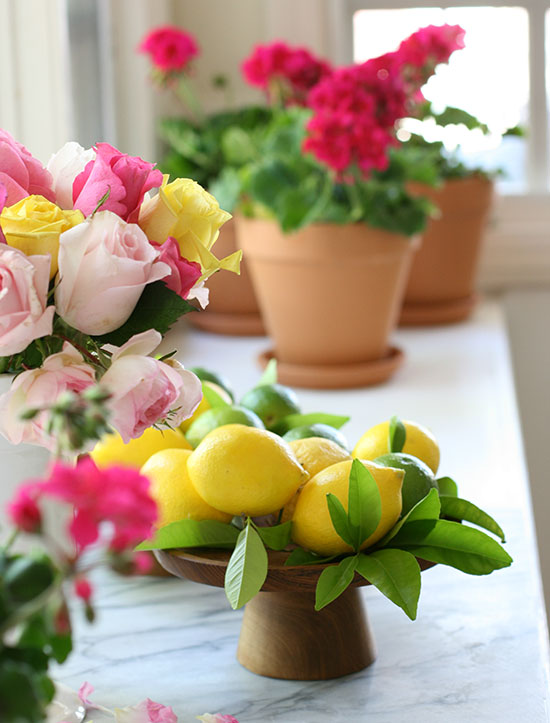 a wooden pedestal full of lemons and potted gernaniums in the background