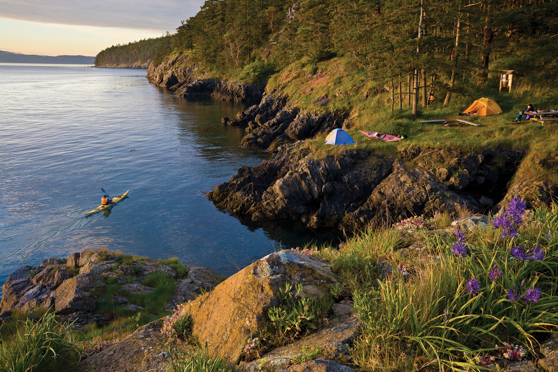 Look out over cliffs leading to the ocean, tents set up on the flatlands and a kayaker in the water.
