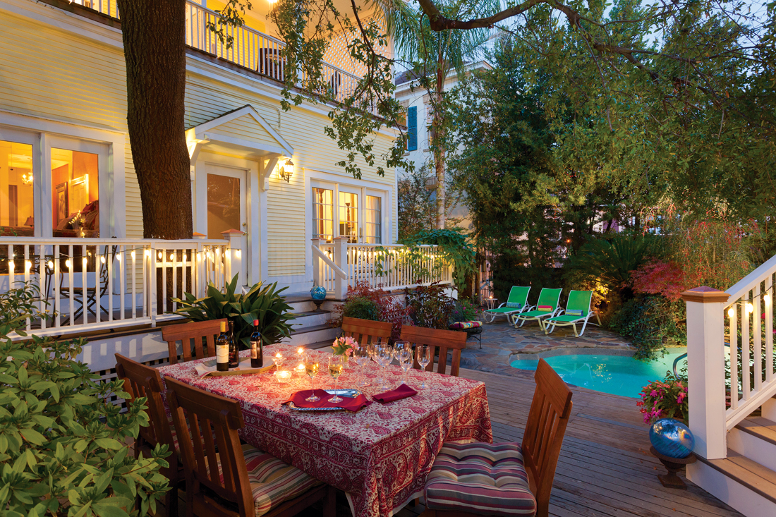 Twilight setting on a back deck with a private spa and dinner table.