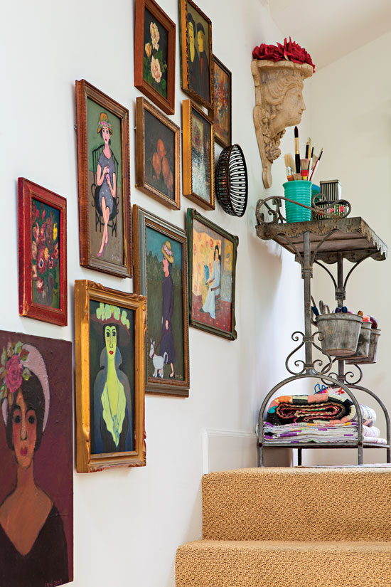 A collection of vintage portrait paintings up a staircase wall