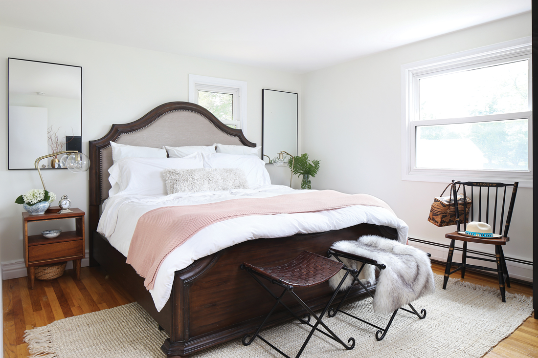 Master bedroom with a substantial dark wooden bed frame and white linens .