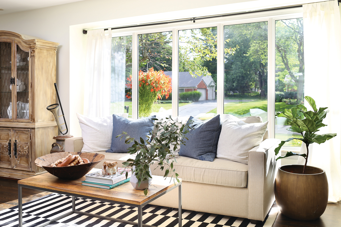 Striped rug with a cream colored cozy couch in front of a huge bright window.