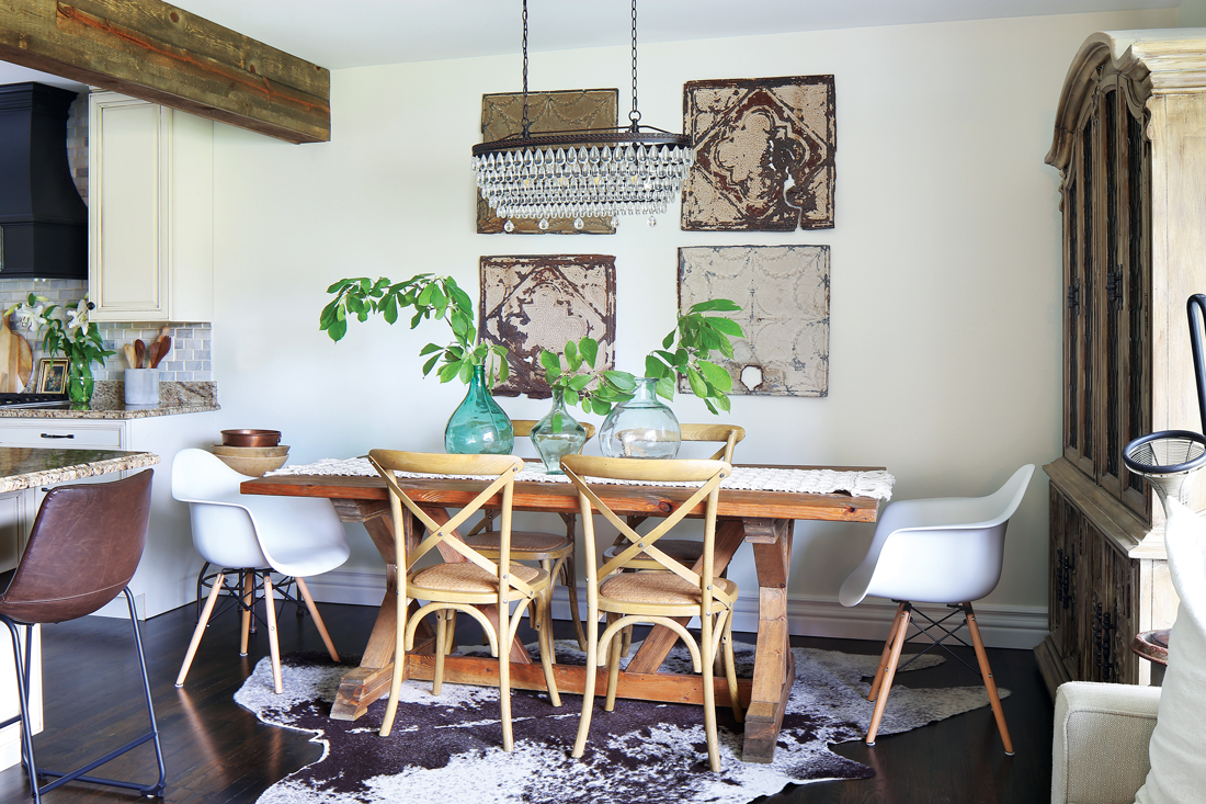 Flea market find and vintage odds and ends give a funky fun look to this dining area off the kitchen. Wooden trestle table and modern bucket chairs with a crystal chandelier.