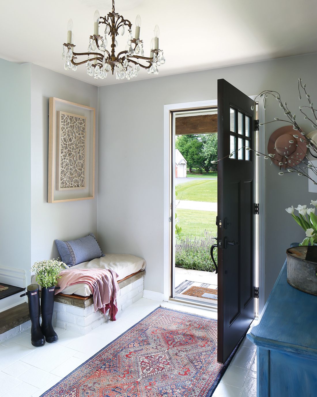 An entry way with a welcoming open door and a vintage Persian runner with an antique chandelier hanging from the ceiling.