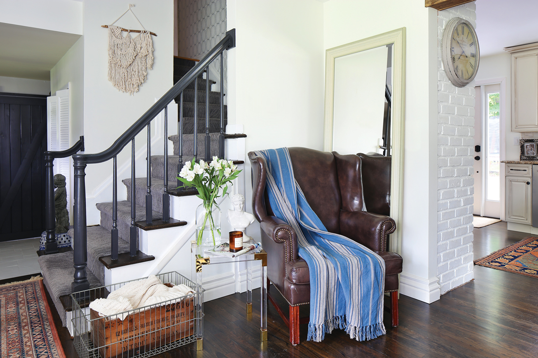 Dark railed stairs frame out a sitting nook with a clear and gold modern endurable and a vintage leather wingback chair.