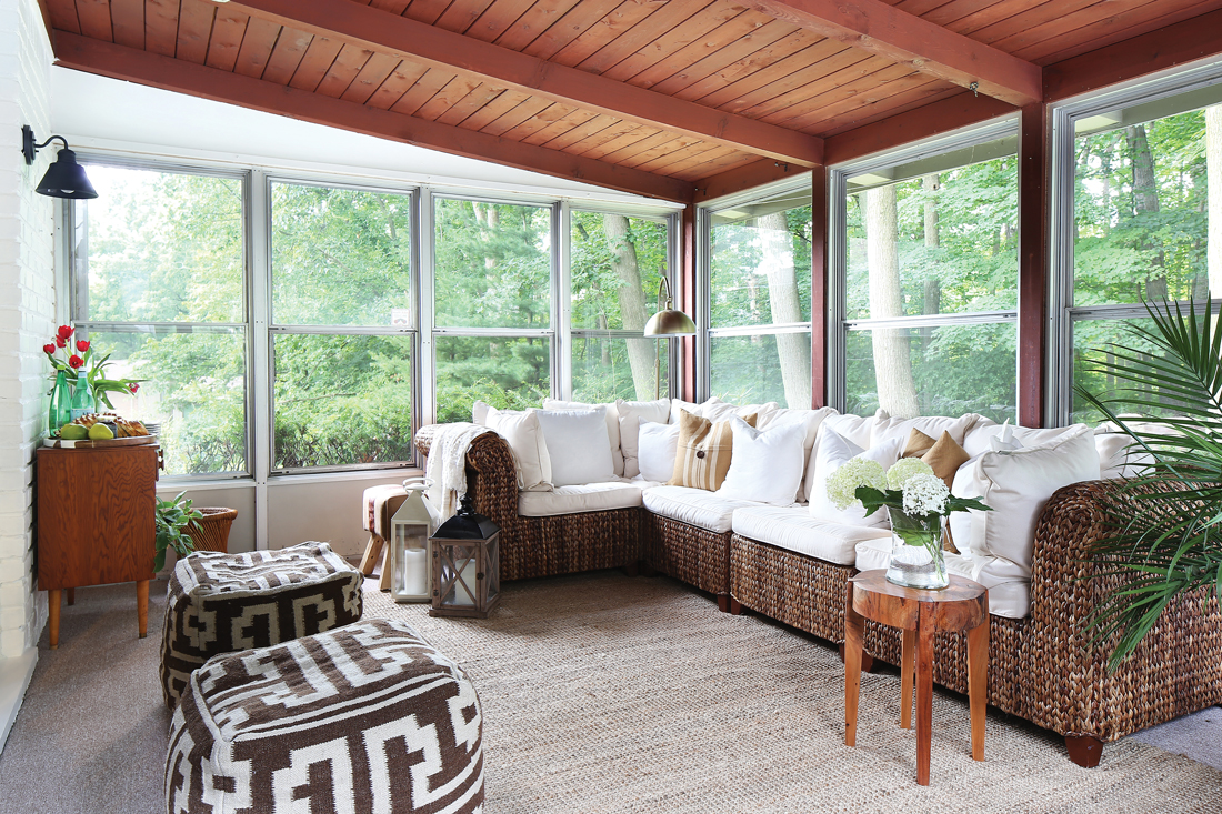 The sun porch overlooks stunning views of nature with a thatched whicker sectional and aztec inspired poofs for additional seating.