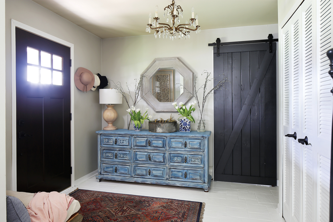 View from the interior of the home at the entryway. The foyer includes a Persian runner, sliding barn door, and an octagonal shaped mirror hanging over a vintage distressed dresser.
