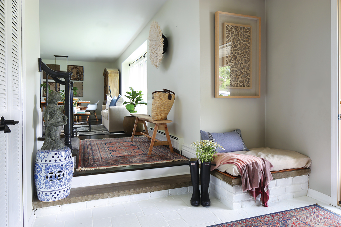 Looking into the living room from the entryway, beckoning you in with Persian rugs and bright window light.