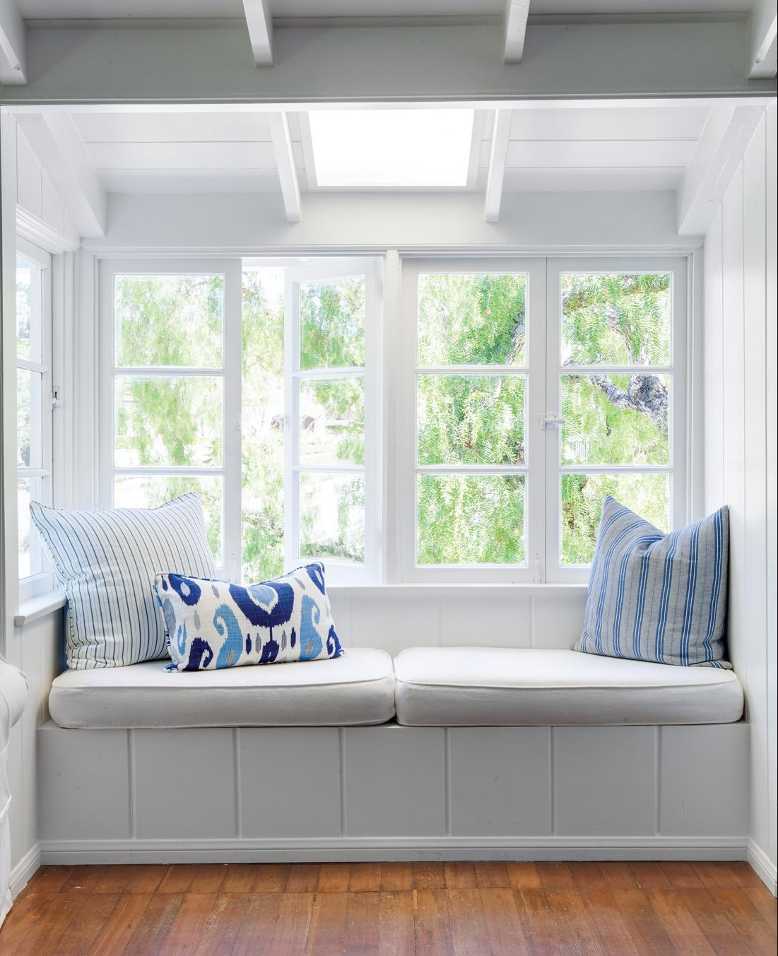 Window seat with all white walls and vaulted ceilings.
