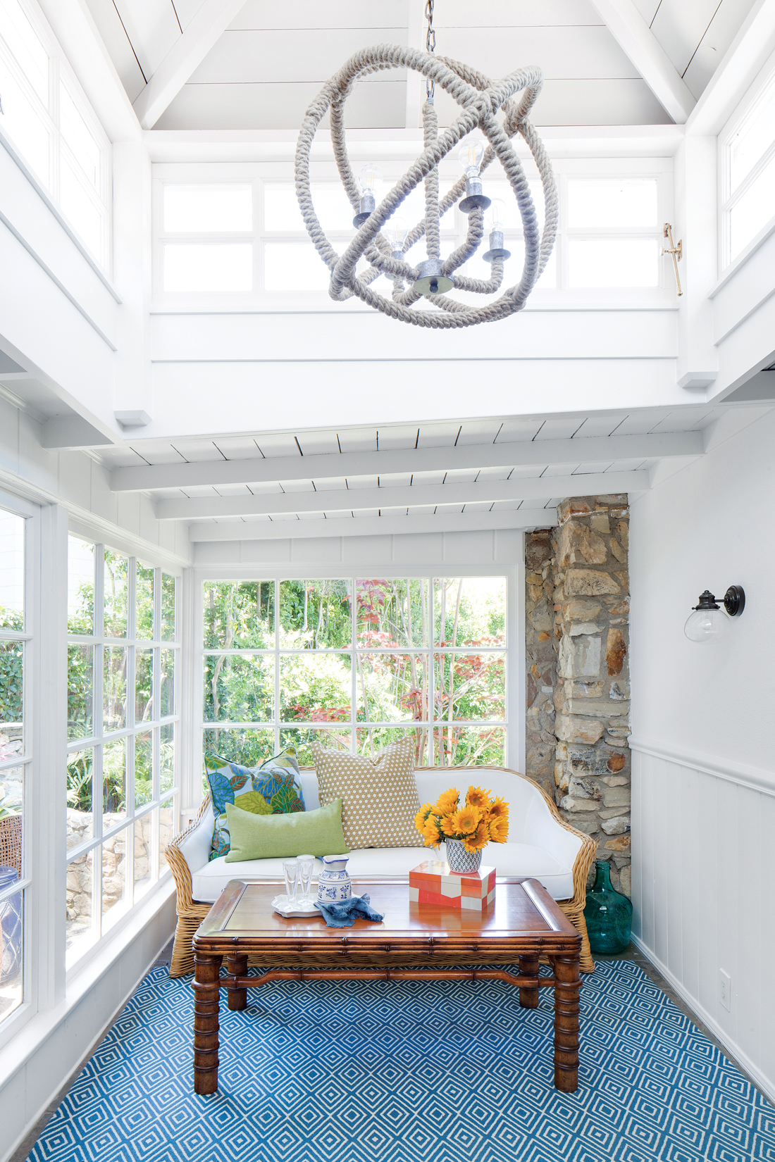 Sun room in a cottage beach house with a white nautical rope light fixture hanging from the vaulted ceiling over a seating area.