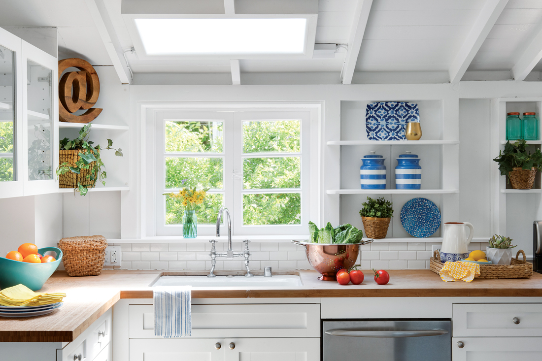 Light and bright kitchen with custom white exposed shelving and butcher block counter-top.