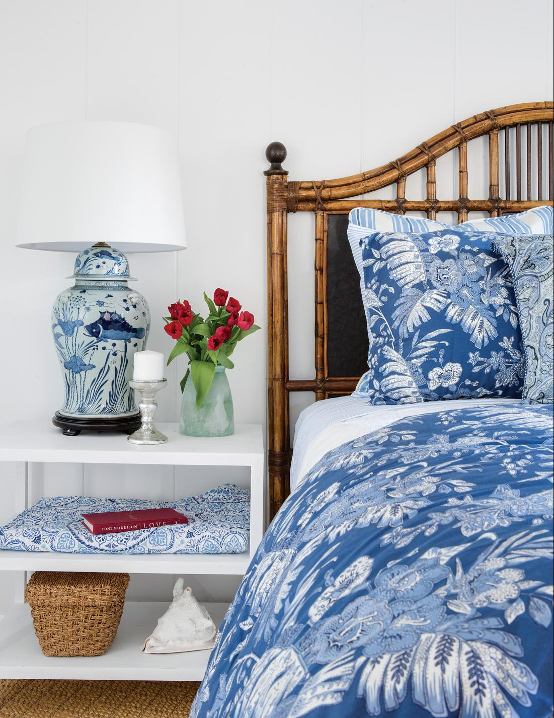 Bedroom with rattan headboard and blue and white accents on the bed and on the nightstand.