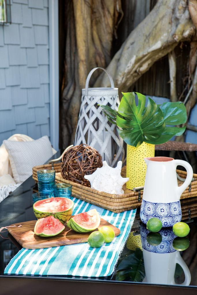 Outdoor table set up for entertaining guests with fresh fruit and beverages.