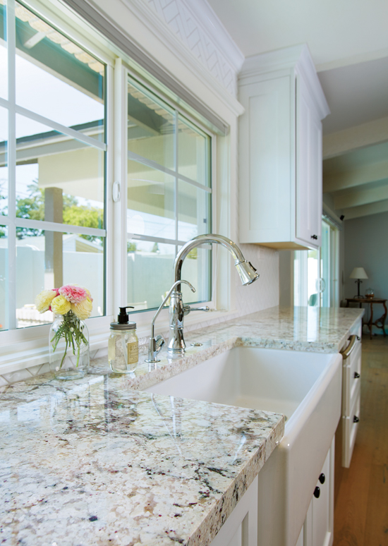 Natural stone granite countertop in a white cabinet kitchen with a farmhouse sink and roses in a glass vase on the counter.