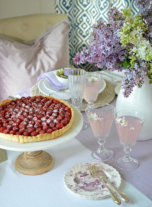 raspberry tart and pink lemonade on a pretty table with lilacs