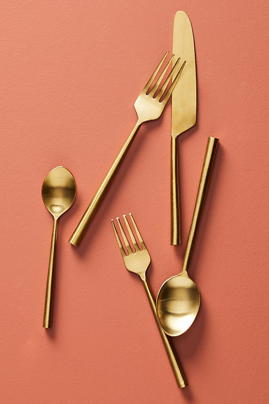 Coral colored backdrop featuring gold plated flatware