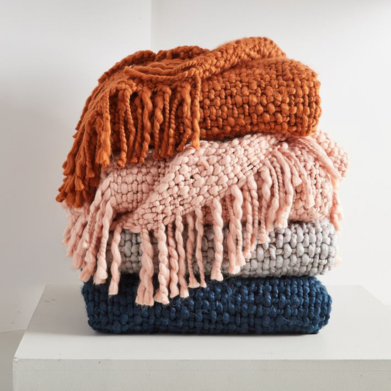 Stack of four colorful fringed throw blankets
