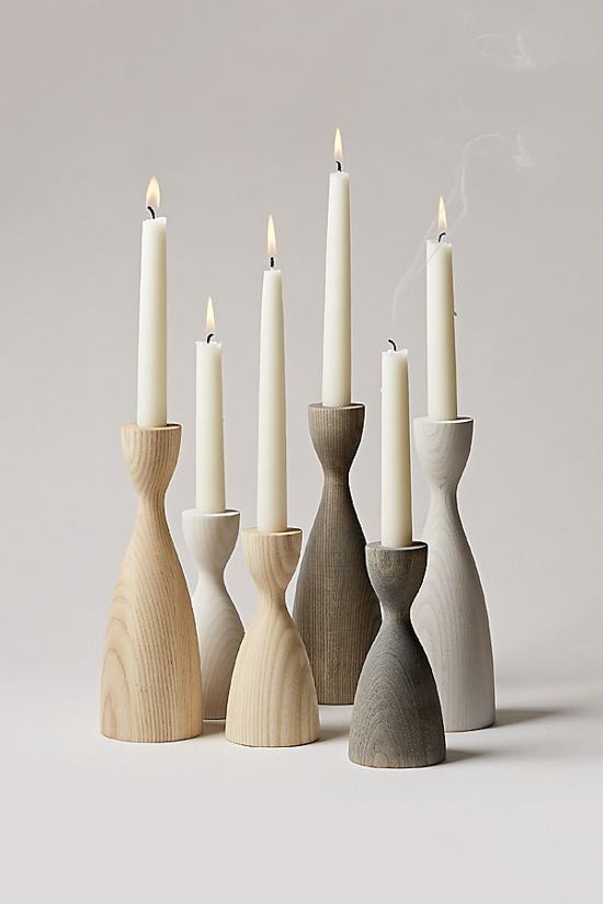 Ombre shaded wooden candlesticks from light wood to gray tone all with white candles lit in them