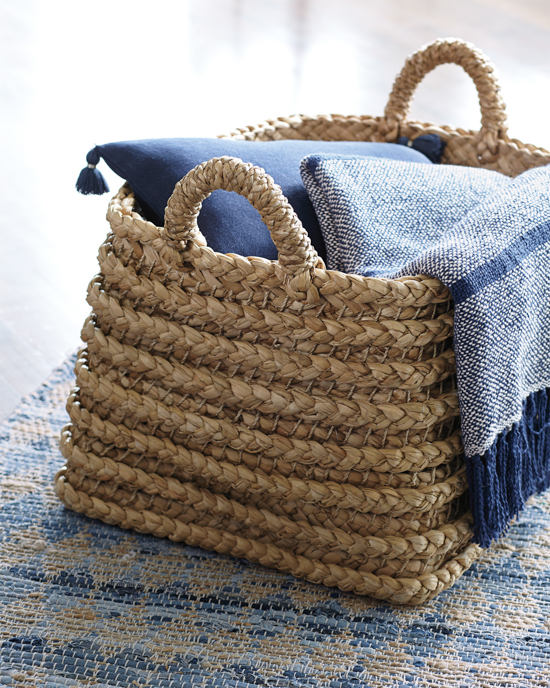 Whicker basket with handles displayed holding a blue pillow and similar colored throw blanket