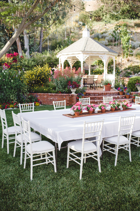 Set outdoor table over looking the yard and white gazebo.