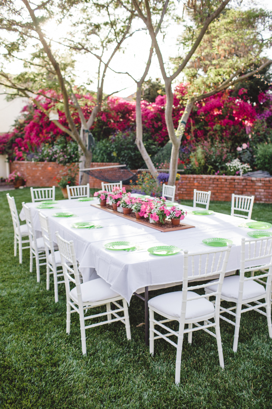 Outdoor table set for guests overlooking a hammock and bougainvillea.