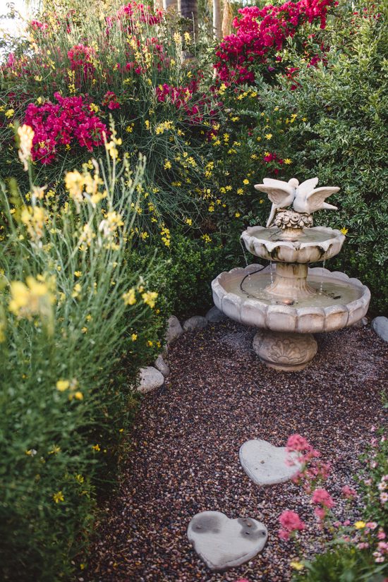 Water fountain with birds on the top and heart shaped stepping stones amongst pea gravel.