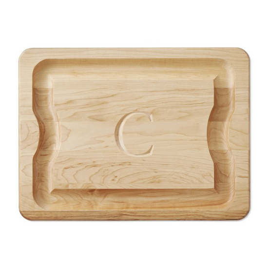 Hand carved wooden cutting board with a monogrammed initial C in the center