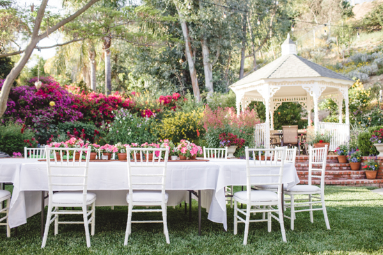 Outdoor table with white table cloths and chairs with a white gazebo in the background.