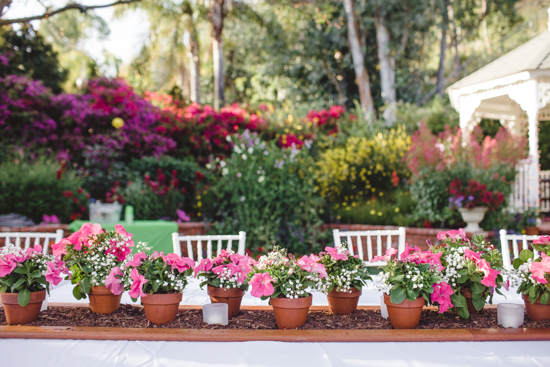 Tablescape on an outdoor seating area topped with pink and white florals in terra-cotta pots.