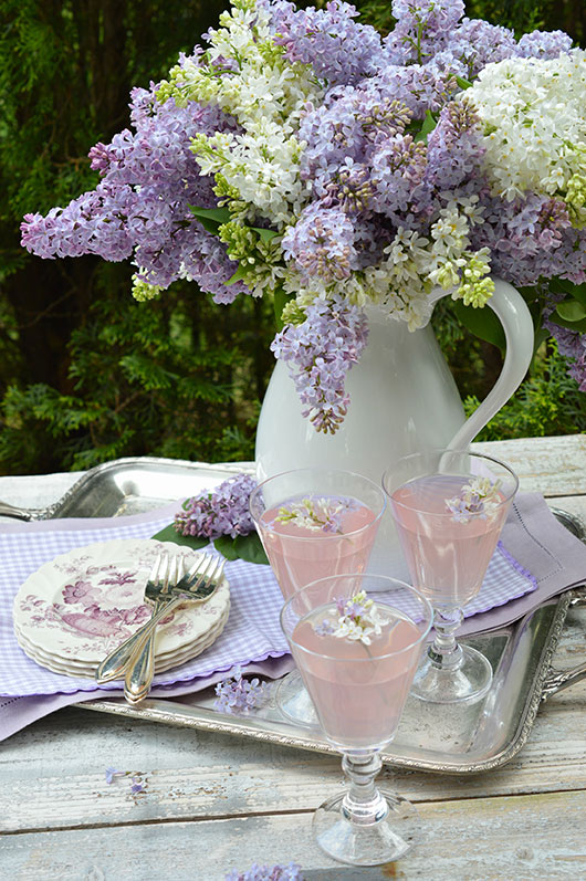 lilacs in a white pitcher on a pretty lavender table setting