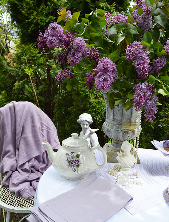 lovely garden table with an urn full of dark purple lilacs