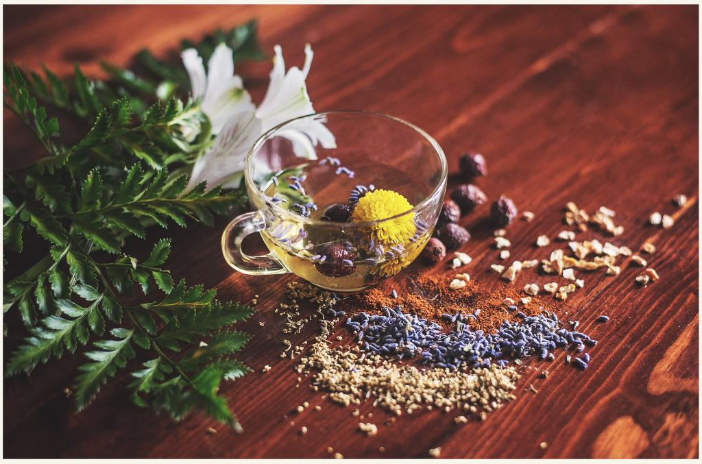 A small glass teacup filled with and surrounded by tea ingredients on a wooden table.
