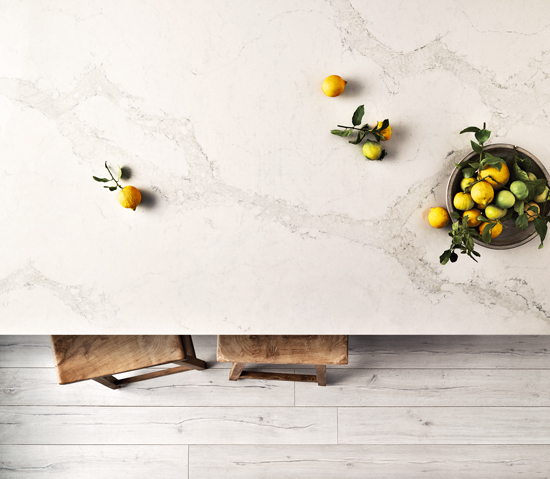 wooden barstools peaking out from under a marble countertop with a bowl of citrus adding color to the countertop.