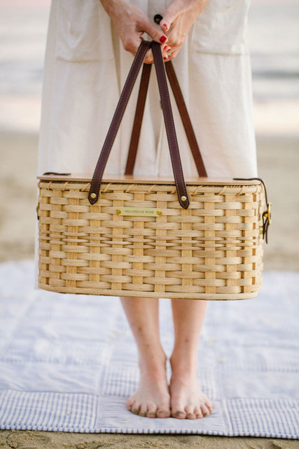Girl standing on the beach in a light colored dress holding a picnic basket.