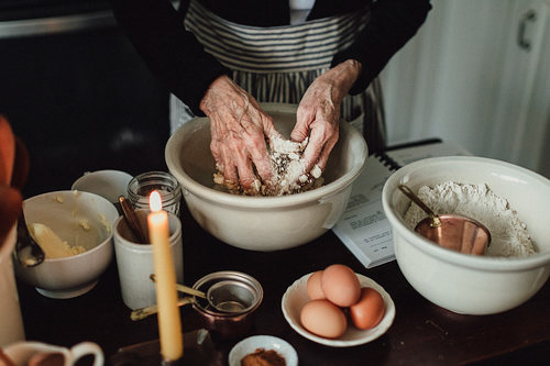 A cluttered table covered in baking supplies and an old woman's hands kneading dough.