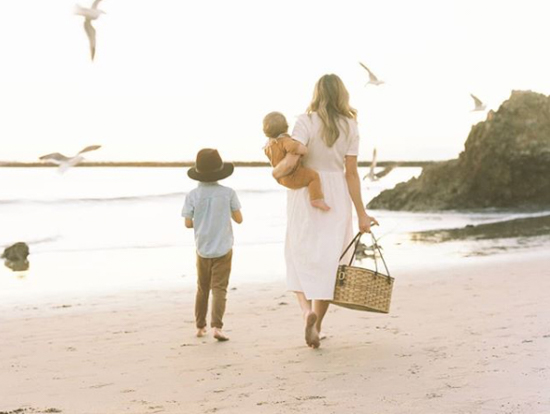 Mother walking with son down the beach during sunset with a baby on one hip and a picnic basket in the other.