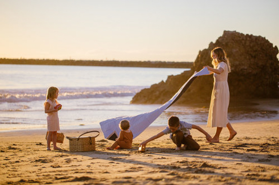 Mother and her three little ones on the beach at sunset laying out a blanket on the sand for a picnic.