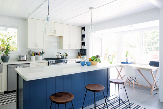 Bright and white kitchen with white quartz countertops and a navy blue paneled island.