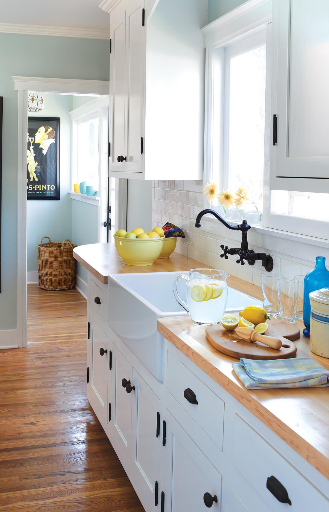 Kitchen with white inlay cabinets and butcher block, wooden countertops.