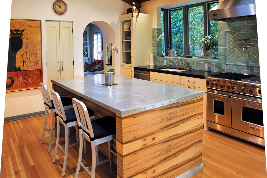 Wooden island with modern silver, zinc countertops with an industrial range in view.