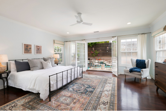 A large bed sits in an iron frame on top of a sprawling Aztec-printed area rug.