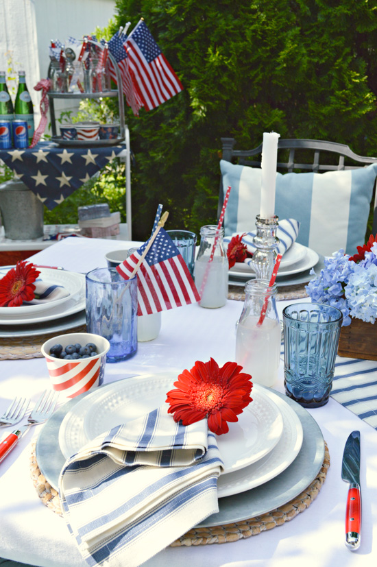 Table set for a meal and decorated in reds whites and blues for the 4th of July.