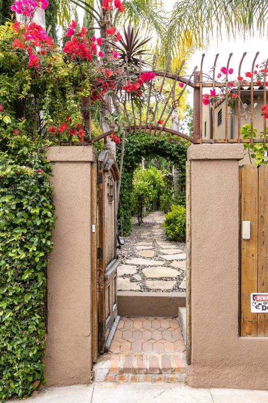 An antique wooden gate covered in bougainvilla opens up to a stone pathway.