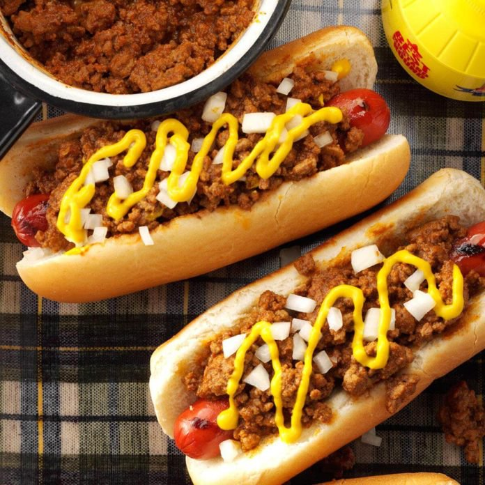 ground beef and mustard are slathered over grilled hot dogs