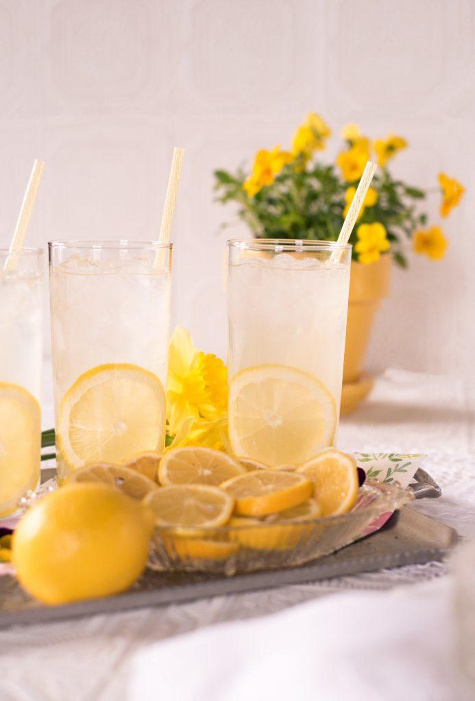 bright yellow lemons sit beside glasses of lemonade