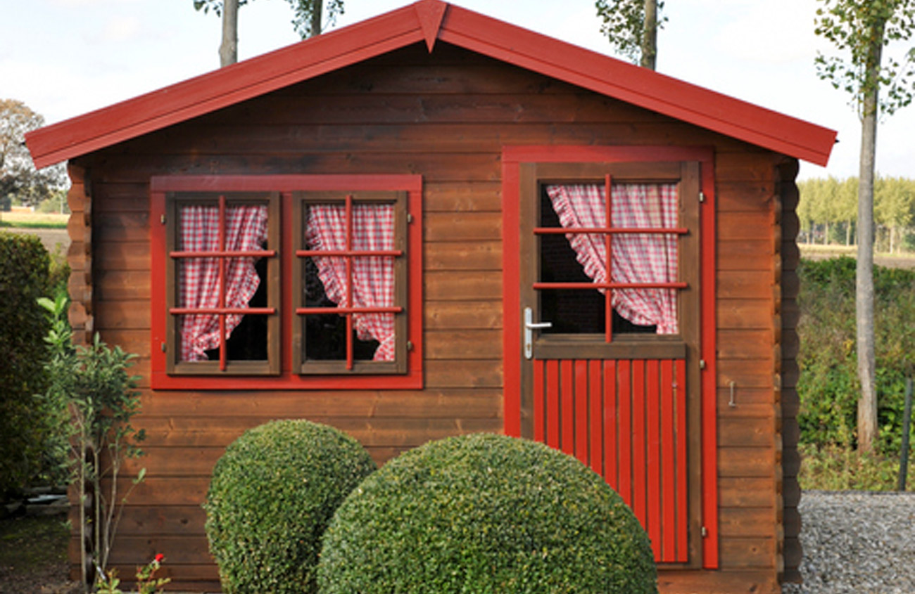 red house with round boxwood shrubs