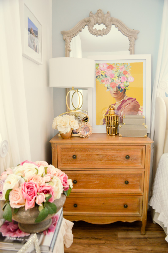 Wooden dresser topped with fresh flowers, gold accents, a large ornate mirror and a pop of colorful art.