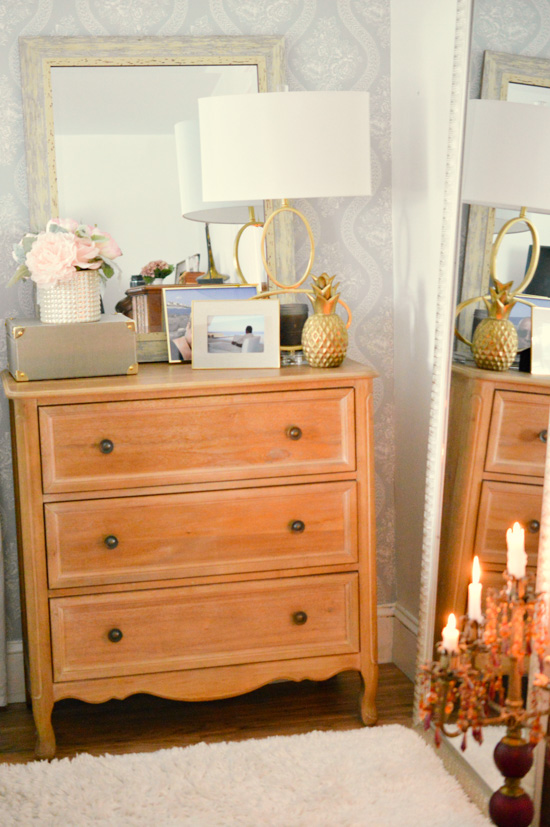 Wooden dresser topped with gold accented frames, romantic floral arrangement and a large mirror and desk lamp.