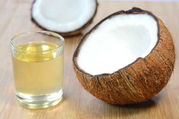 A glass of coconut oil next to an open fresh coconut