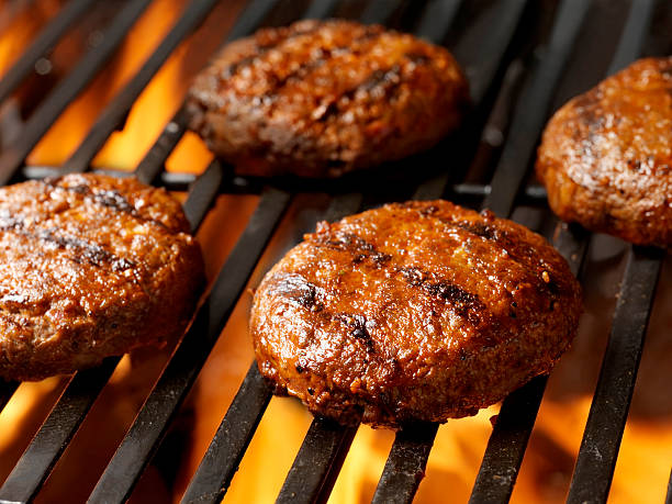 burger patties sit on a fired-up grill